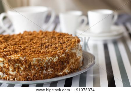 Homemade Delicious Honey Cake With Crumb. White Tea Set On Background. Selective Focus.