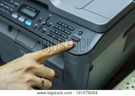 Finger pressing start button of fax machine office equipment