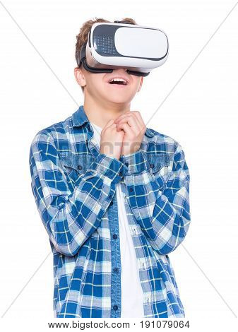 Amazed teen boy screaming, wearing virtual reality goggles watching movies or playing video games. Surprised teenager looking in VR glasses. Child experiencing 3D gadget technology.