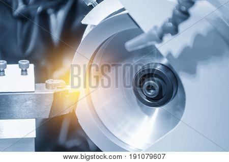 The abstract scene of the grinding machine grinding the lath cutting tool with the glowing edge lighting effect