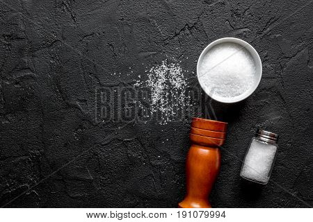 salt in glass bottle with saltcellar for spices set on dark table background top view mockup