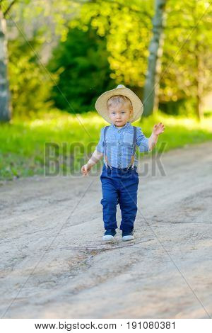 Portrait of toddler child outdoors. Rural scene with one year old baby boy wearing straw hat