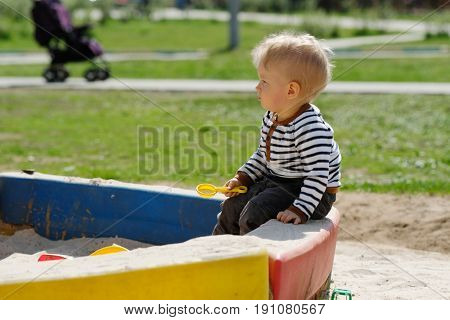 Portrait of toddler child outdoors. One year old baby boy playing with sand at playground sandbox