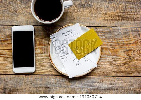 credit card for paying, mobile, cup of coffee and check on cafe wooden desk background top view mock up