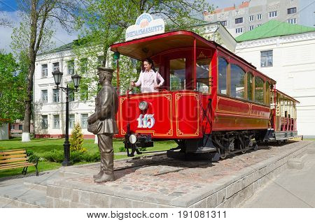 VITEBSK BELARUS - MAY 21 2017: Monument to first Vitebsk tram and monument to conductor Belarus. Unknown woman is in cab of tram car in driver's seat