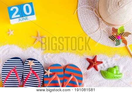 June 20th. Image of june 20 calendar on yellow sandy background with summer beach, traveler outfit and accessories. Summertime concept.
