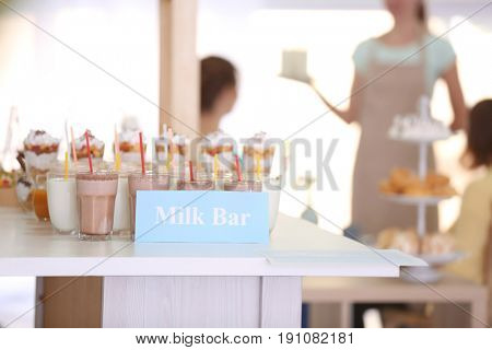 Different drinks and desserts with visitors sitting in milk bar