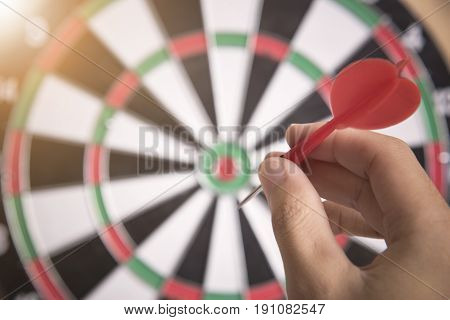 hand holhing red arrow target center of dartboard. concept business goal to marketing success.