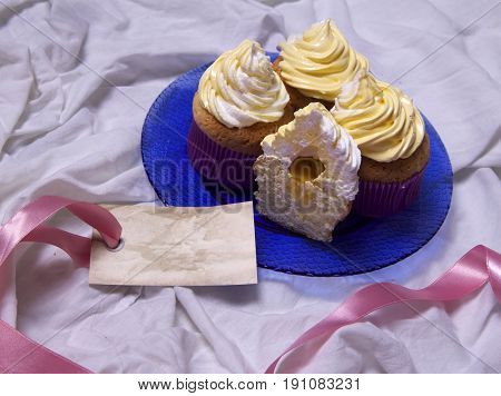 delicious freshly baked homemade lemon muffins cupcakes with butter cream on a plate on the table copy space