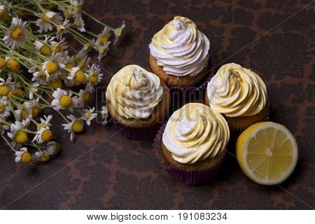 delicious freshly baked homemade lemon muffins cupcakes with butter cream with bouquet of chamomile flowers copy space