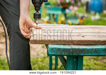 Man with drill works in park during day