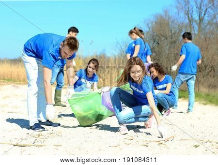 Young volunteers gathering garbage outdoors