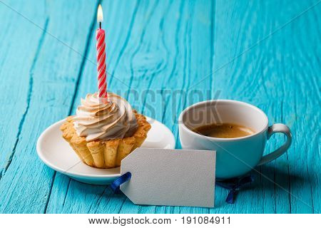 Shortcake with cream and a candle, with a cup of coffee and a blank card on a blue table