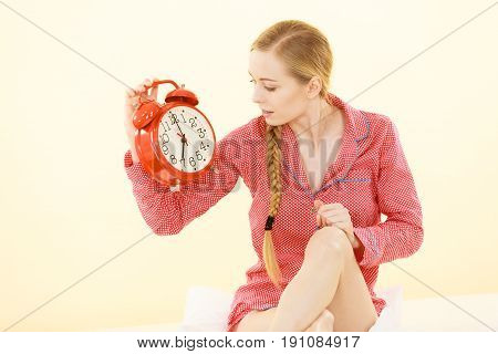 Sleepy Woman Wearing Pajamas Holding Clock
