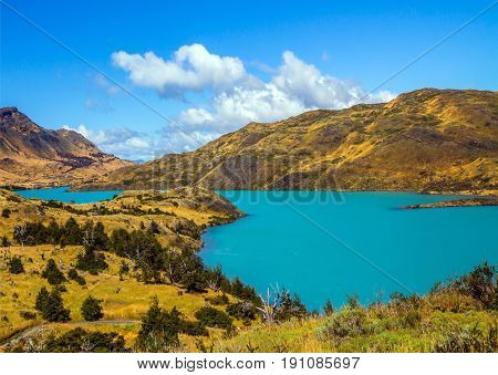 Torres del Paine National Park. Rio Paine - quiet river flow among the picturesque yellow hills. Summer in the south of Chile. The concept of extreme and active tourism