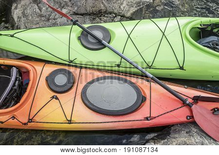 Two kayaks are moored on the rocky shore of the sea. Top view.
