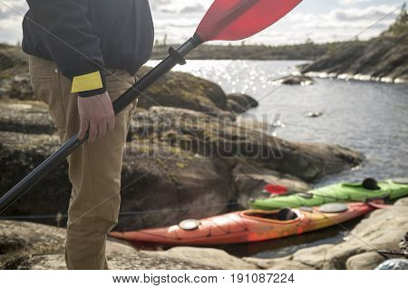 Man with a paddle stands on a rocky shore against a background of two moored kayaks a lake and a sky in a cloud.