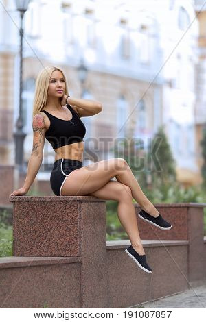Beautiful strong blonde tattooed girl sitting on the street outdoor at the evening in shorts and showing her perfect abdominal muscles.