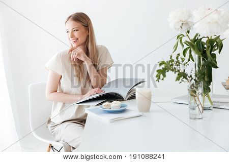 Image of young happy woman sitting indoors reading book. Looking aside.