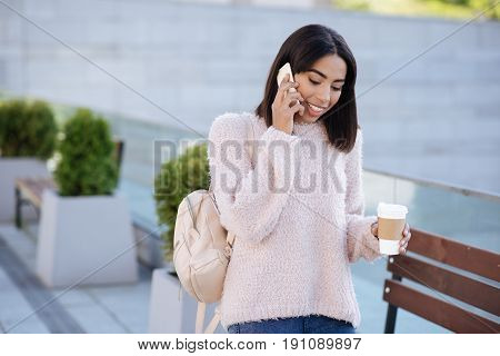 Always walking. Pretty outgoing positive woman using her smartphone for calling her acquaintance and asking her out for a coffee