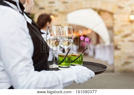 Midsection of professional waiters in uniform serving wine, cocktails and snacks during buffet catering party, festive event or wedding. Full glasses of wine on tray. Outdoor party catering service