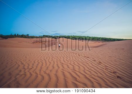 The Boy Runs Around The Red Desert At Dawn. Traveling In A Fuss With Children Concept