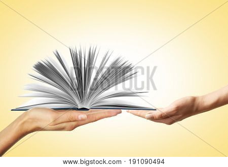 Concept of right to education. Female hands with book on color background