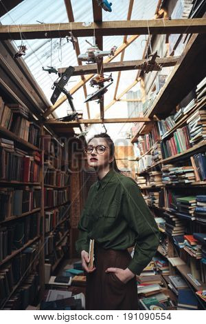 Portrait of young woman in glasses holding book and hand in pocket in library. Looking camera