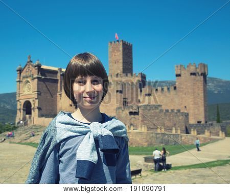 Young boy posing and smiling over ancient spanish castle Javier, Navarre, Spain. Cultural and historical spanish heritage. Young tourist agains architectural sight, image toned