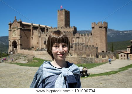 Beautiful 11 years old boy posing and smiling over ancient spanish castle Javier, Navarre, Spain. Cultural and historical spanish heritage. Young tourist agains architectural sight, image toned