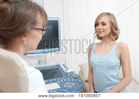 Young woman having an appointment with her doctor discussing survey results on a monitor of ultrasound scanner clinic medicine people healthcare professionalism help concept.