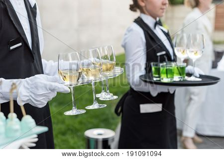 Midsection of professional waiters in uniform serving wine and snacks during buffet catering party, festive event or wedding. Full glasses of champagne on tray