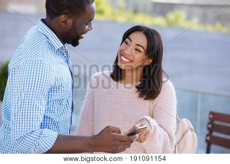 Memories on phone. Emotional clever easygoing man meeting his friend and telling her about his recent trip while showing photos on his smartphone