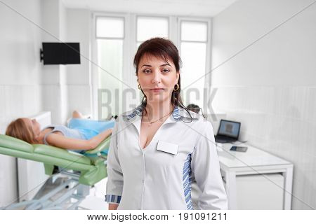 Mature female doctor posing confidently at the hospital female patient lying on gynecological chair on the background medicine healthcare feminine health gynecology professionalism trust.