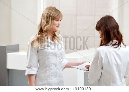 Shot of two young female nurses examining papers together copyspace paperwork working profession occupation job career hospital clinic healthcare medicine.
