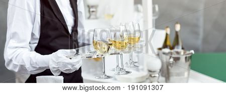 Midsection of professional waiter in uniform serving wine during buffet catering party, festive event or wedding. Full glasses of champagne on tray