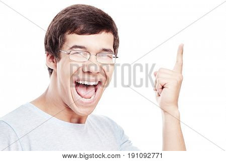 Young excited hispanic man wearing glasses and blue t-shirt standing and pointing aside with his index finger isolated on white background - choice concept