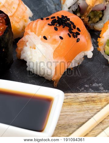 piece of nigiri on slate and around them soy sauce and other sushi pieces