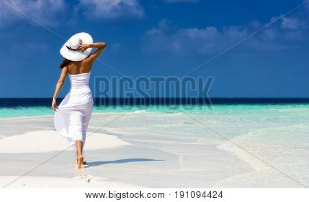Girl in white on a sandbank in the Maldives