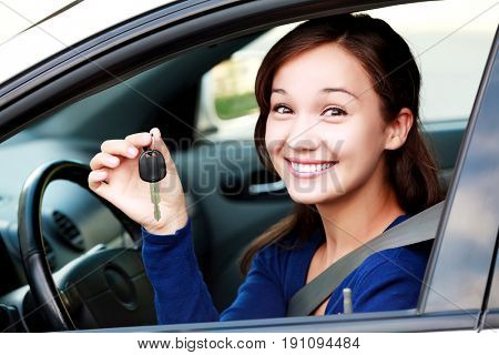 Beautiful young smiling happy girl shows the car key in her hand