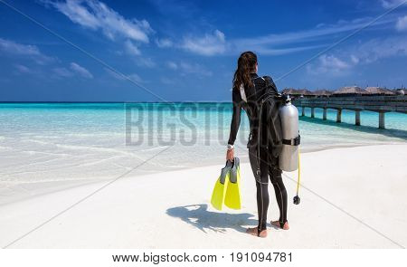 Female scuba diver with diving equipment on the beach at the Maldives
