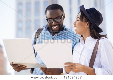 Promising numbers. Young analytical competent guy looking excited while perusing a report his colleague bringing for sharing with him