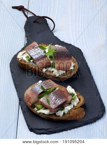 Delicious Sandwiches with Marinated Herring Cream Cheese and Chives on Slices of Brown Bread closeup on Slate Board on Wooden background