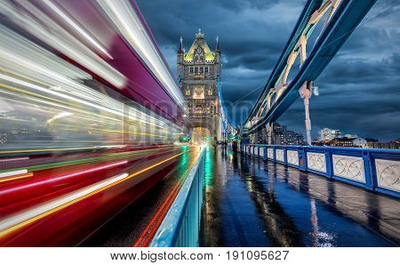 Moving red bus on Tower Bridge in London