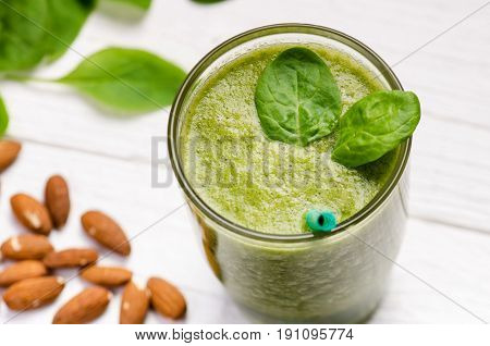 Spinach smoothie on a wooden white background. Glass of smoothie with two leaves of spinach. Nuts. Healthy food. Breakfast.