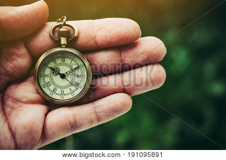 An ancient pocket watch placed on hand.
