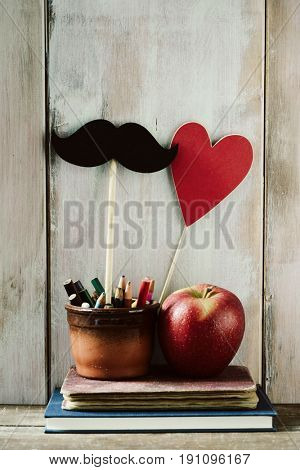 some pencils, a moustache and a red heart attached to sticks in an earthenware pot, a red apple and some books on a rustic wooden desk, against an off-white rustic wooden background