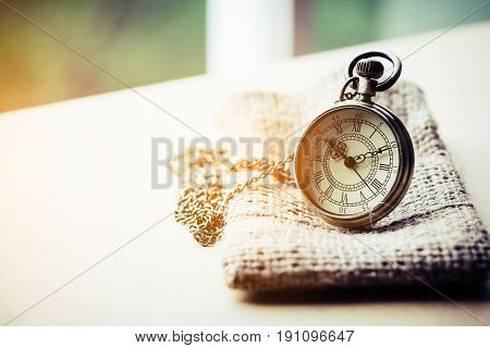 Time concept - Pocket watch on sack in mild sunshine.