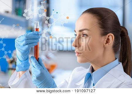 Young female chemist with test tube in hands