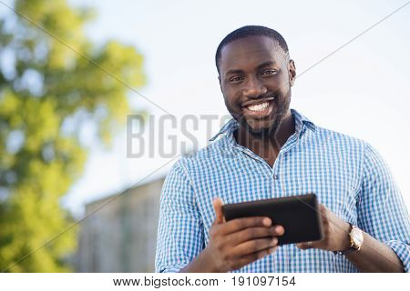 Instant communication. Bright expressive attractive man writing a new post and reading feedback while using his smartphone and internet connection